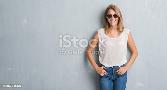 istock Beautiful young woman standing over grunge grey wall wearing fashion sunglasses with a happy face standing and smiling with a confident smile showing teeth 1056774008