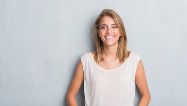 美麗的年輕女子站在那灰濛濛的牆上, 一張幸福的臉站著, 面帶微笑, 露出自信的微笑, 露出牙齒 - 年輕女性 個照片及圖片檔