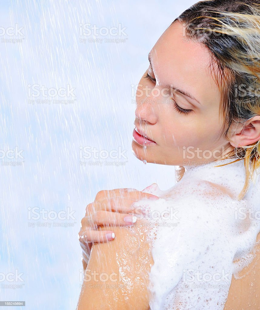 Beautiful young woman standing under streams of water stock photo
