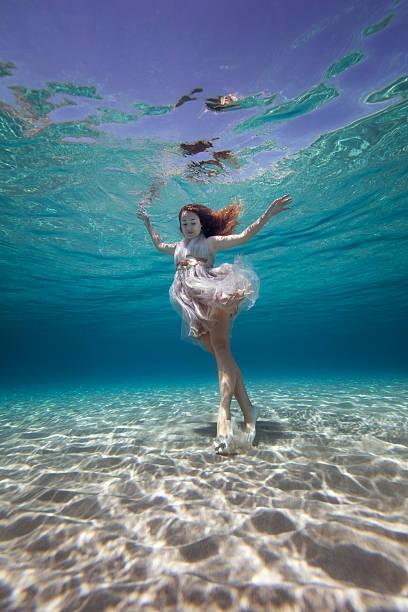 schöne junge frau stehend unterwasser - meerjungfrau kleid stock-fotos und bilder