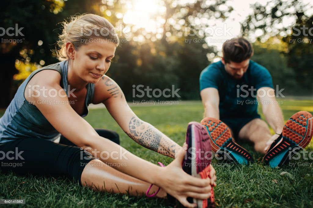 Beautiful young woman stretching with man stock photo