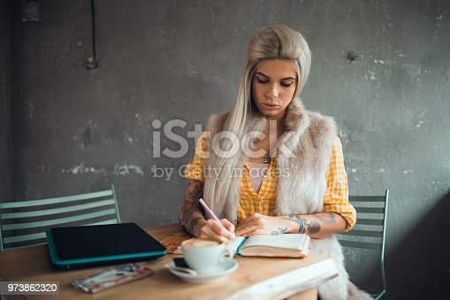 1183295518 istock photo Beautiful young woman studying and writing in the coffee bar 973862320