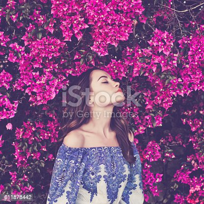 istock Beautiful young woman surrounded by flowers 611878442