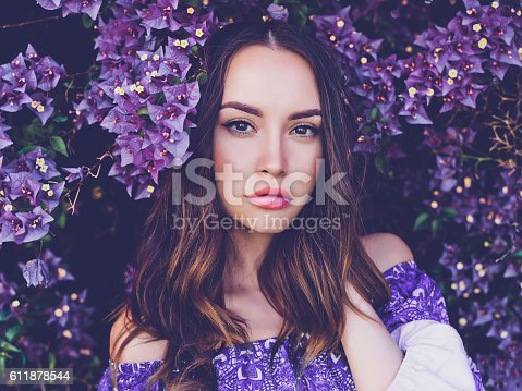 istock Beautiful young woman surrounded by flowers 611878544