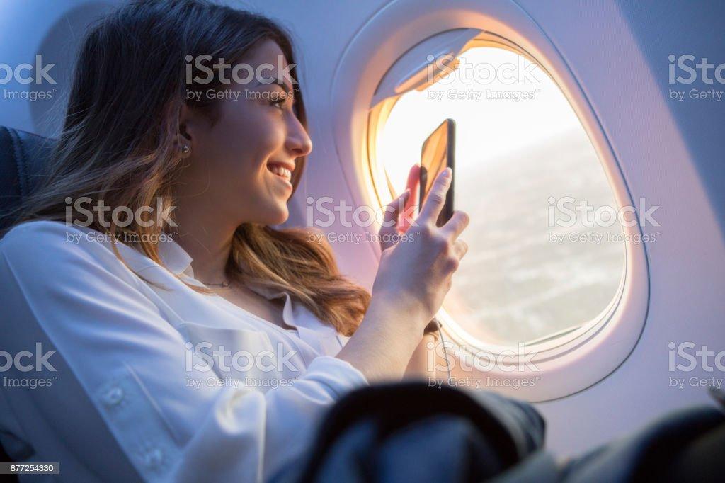 Hermosa mujer joven toma fotografía puesta de sol desde avión - foto de stock
