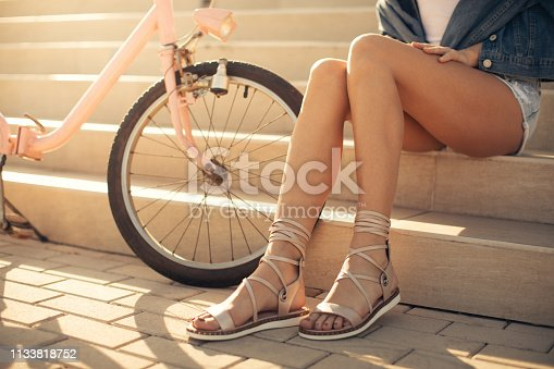 Young woman sitting and relaxing on stairs outdoors after cycling at beautiful sunny day