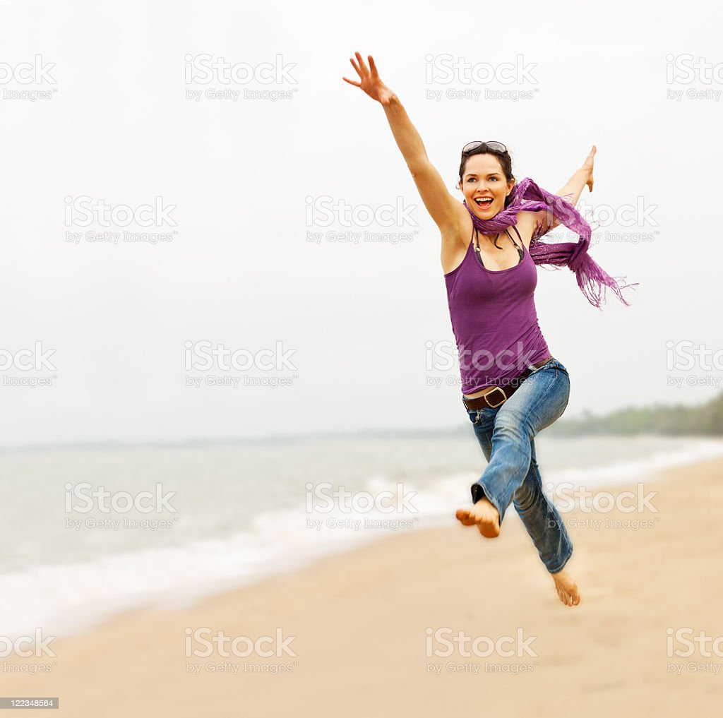 Beautiful young woman taking a great leap on the beach stock photo