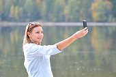 istock Beautiful young woman taking a selfie in nature 471059408