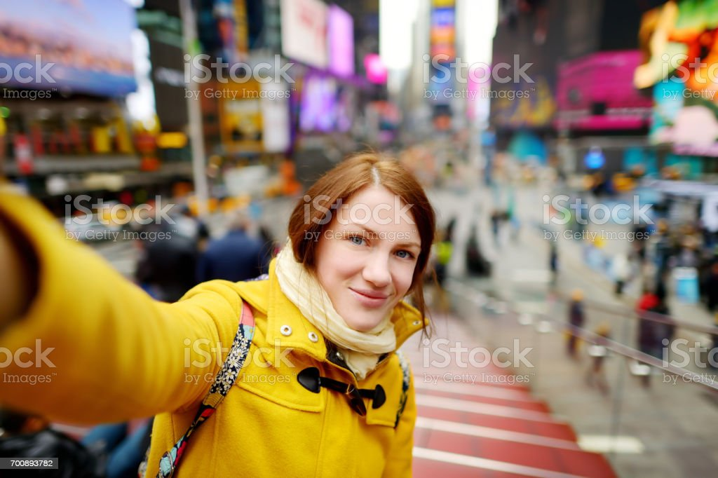Beautiful young woman taking a selfie with her smartphone on Times Square stock photo
