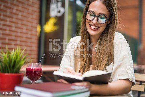 Beautiful young woman taking notes in her diary at cafe garden.