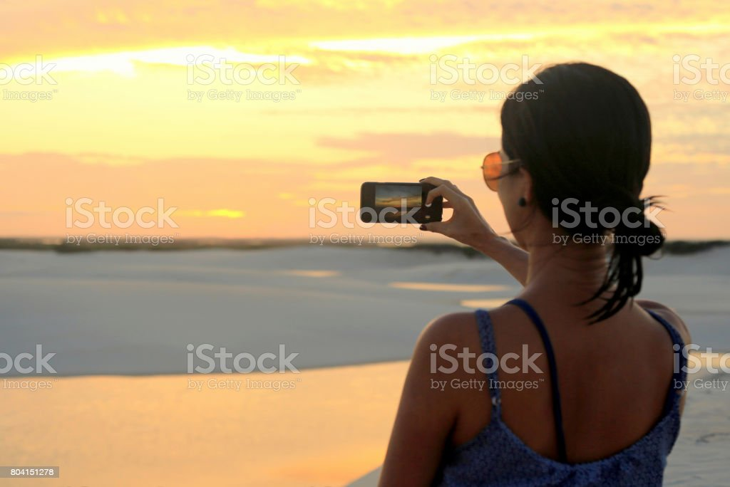 Beautiful young woman taking photo of the sunset