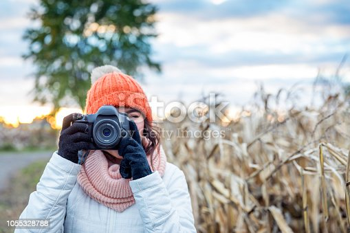 Beautiful Young Woman Taking picture with Digital Camera at Sunset in a Corn Field.