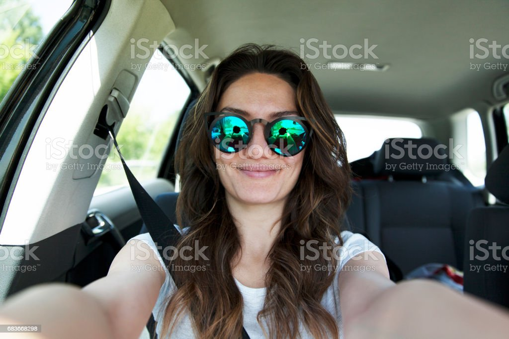 Beautiful young woman taking selfie in car seat belt fastened stock photo
