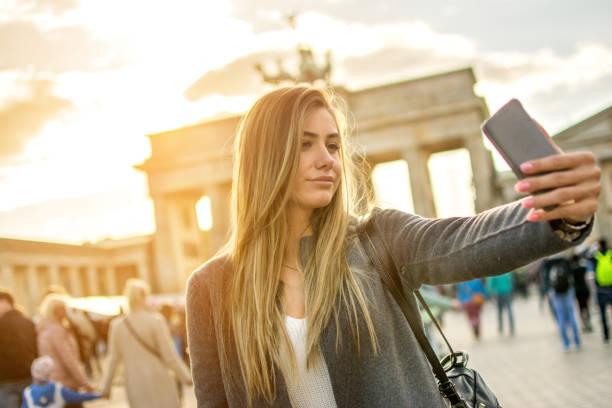 schöne junge frau selfie aufnahme vor dem brandenburger tor in berlin bei sonnenuntergang. - ikonische frauen stock-fotos und bilder