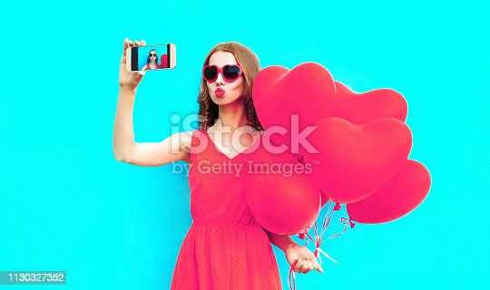 istock Beautiful young woman taking selfie picture by phone with pink heart shaped air balloons on colorful blue background 1130327352