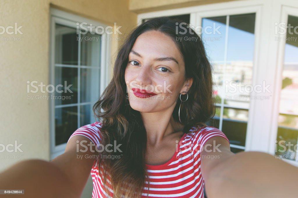 Beautiful young woman taking selfie stock photo
