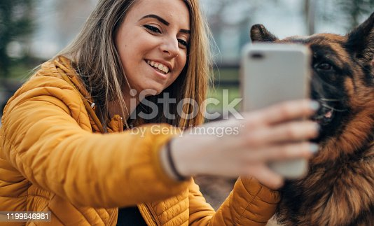 636418612 istock photo Beautiful young woman taking selfie with dog in the park 1199646981