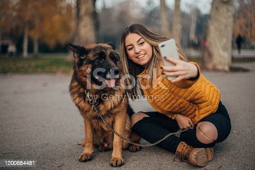 636418612 istock photo Beautiful young woman taking selfie with dog in the park 1200684481