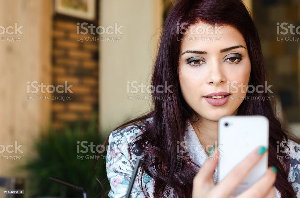 Beautiful young woman  talking on the phone with video call stock photo