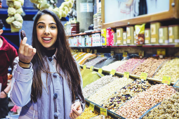 Beautiful young woman tastes dates fruit in Grand Bazaar, Istanbul, Turkey stock photo