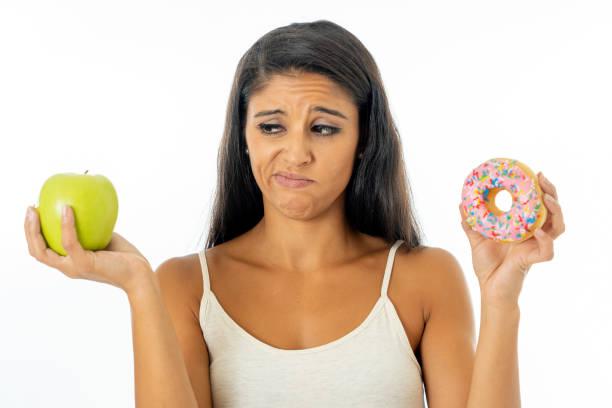 bela jovem tentado fazer escolha entre apple e rosca em saudável alimentos pouco saudáveis, desintoxicação alimentar, calorias e conceito de dieta. - junk food - fotografias e filmes do acervo