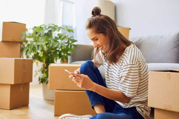 Beautiful young woman texting while moving to new apartment Beautiful young woman texting while moving to new apartment physical activity stock pictures, royalty-free photos & images