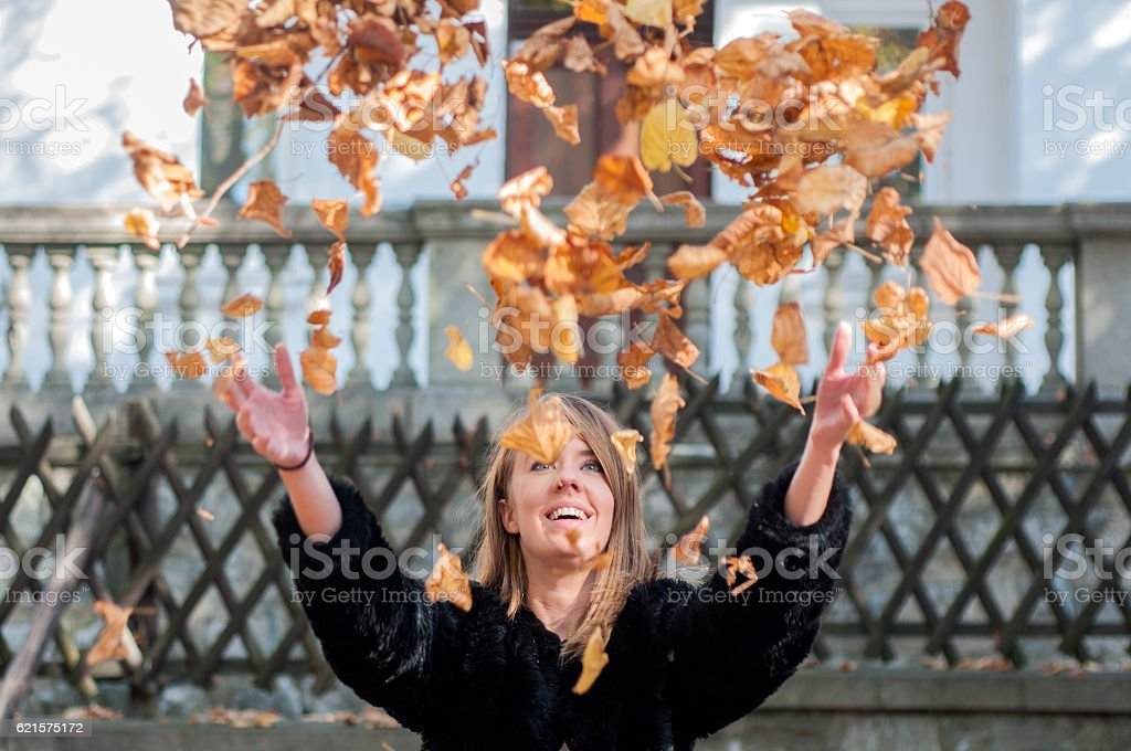 Beautiful young woman throwing leaves in a park, enjoying photo libre de droits