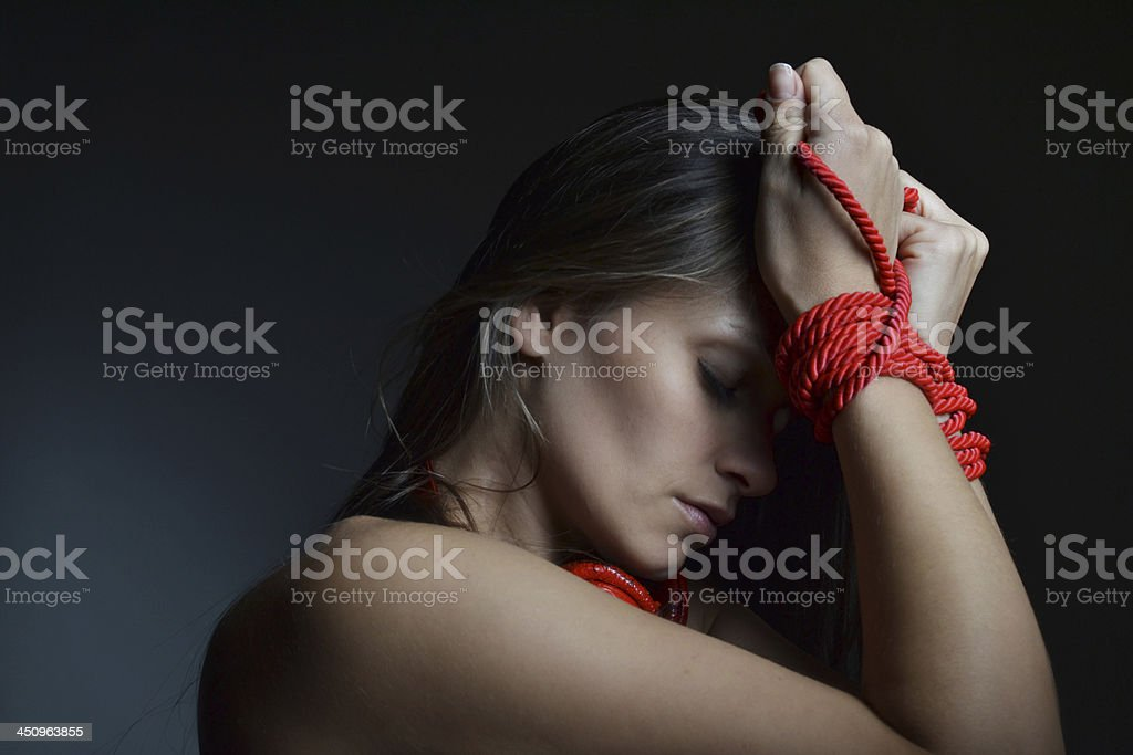 beautiful young woman tied with the red rope stock photo