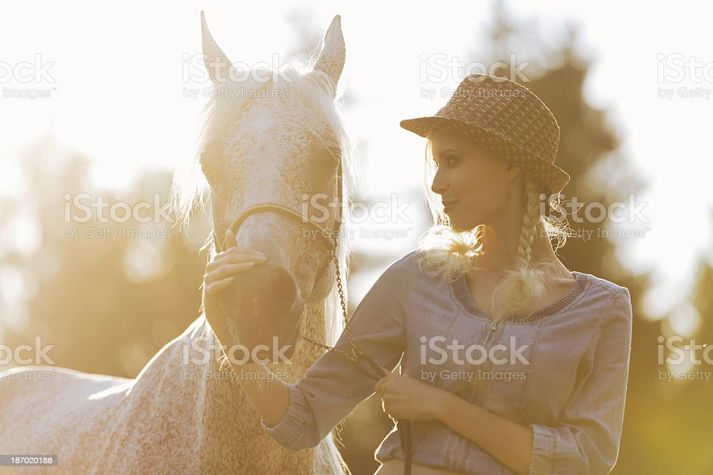 Beautiful young woman together with white horse in summer royalty-free stock photo