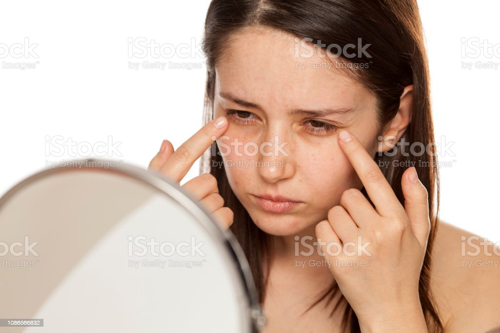 Beautiful Young Woman Touch Her Face Under Eyes In Mirror On