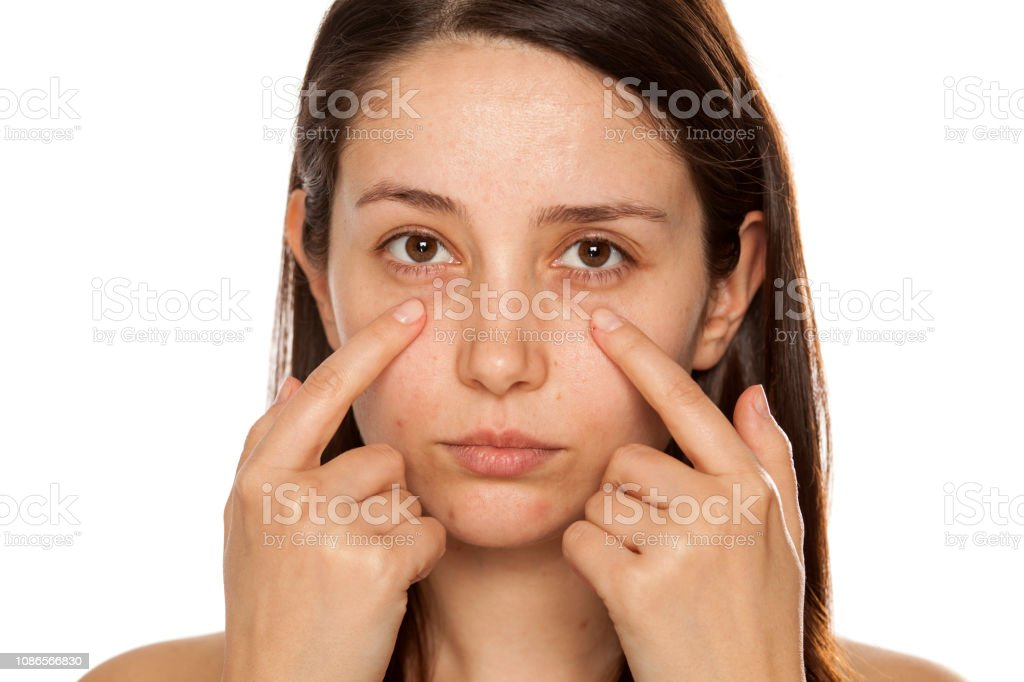 Beautiful young woman touch her face under eyes on white background stock photo