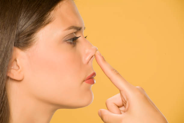 Beautiful young woman touching her nose with her finger on yellow background stock photo