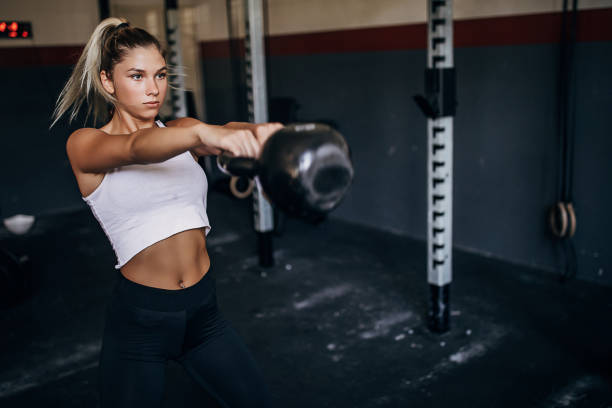 Beautiful young woman training with kettlebell in gym stock photo