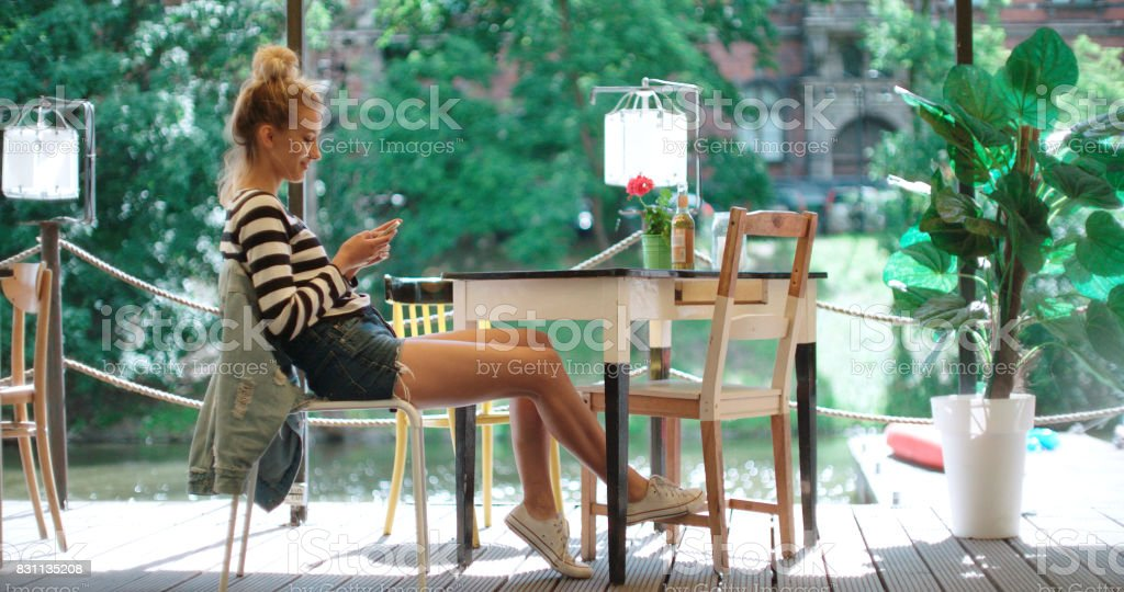 Beautiful young woman typing on phone during sunny day in an outdoors cafe. stock photo