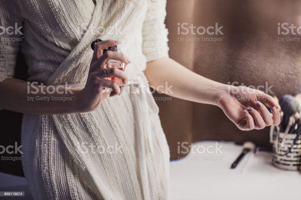 Hermosa mujer joven usa botella de perfume en casa, closeup - foto de stock
