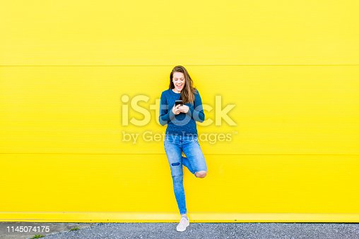 Beautiful Young woman Using a smart phone against vivid Yellow background