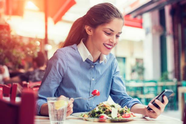 サラダを食べながら彼女のスマート フォン デバイスで sms メッセージを送信するアプリケーションを使用して美しい若い女性 - 昼食 ストックフォトと画像
