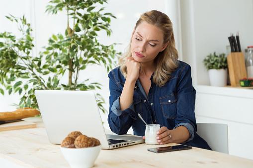 Foto de Mulher Jovem E Bonita Usando Seu Laptop E Comer Iogurte Em Casa e mais fotos de stock de Adulto