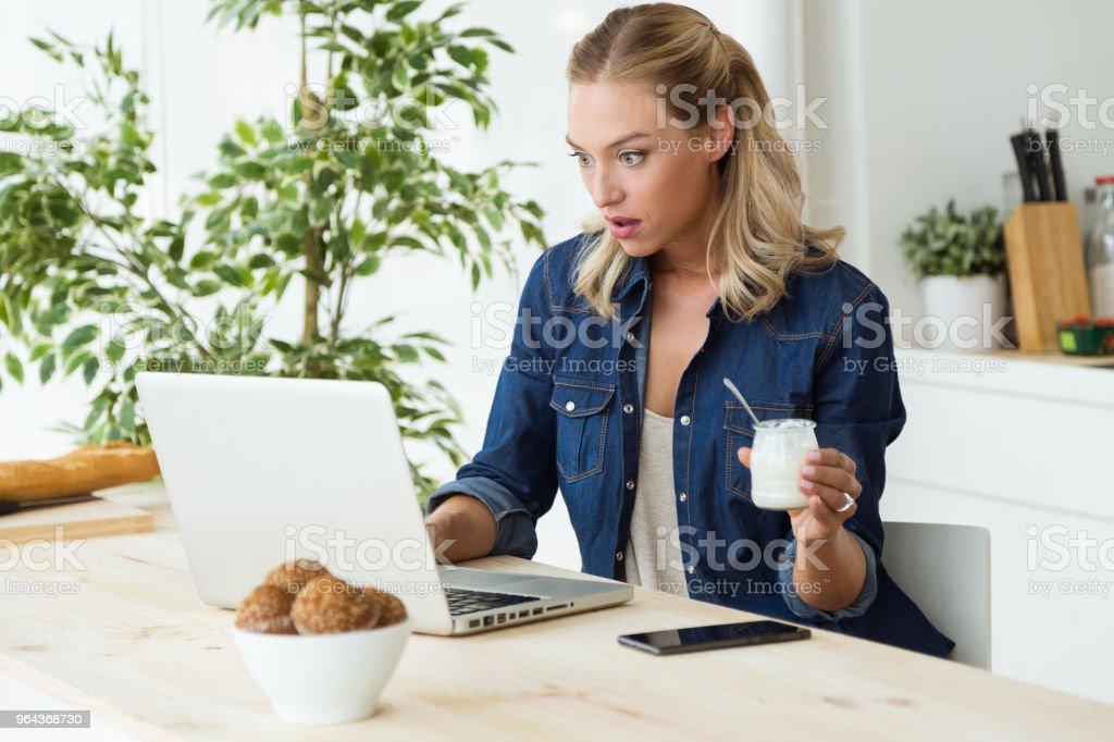 Mulher jovem e bonita usando seu laptop e comer iogurte em casa. - Foto de stock de Adulto royalty-free
