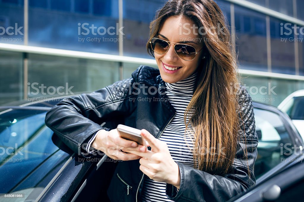 Beautiful young woman using her mobile phone in the car. stock photo