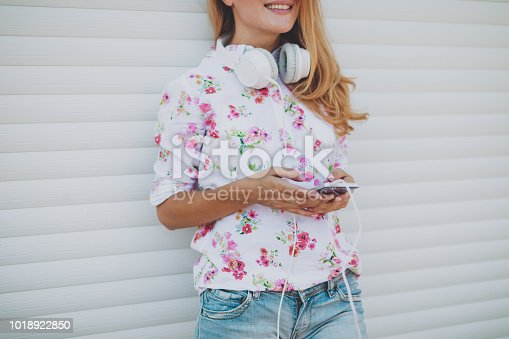 istock Beautiful young woman using mobile in the street 1018922850