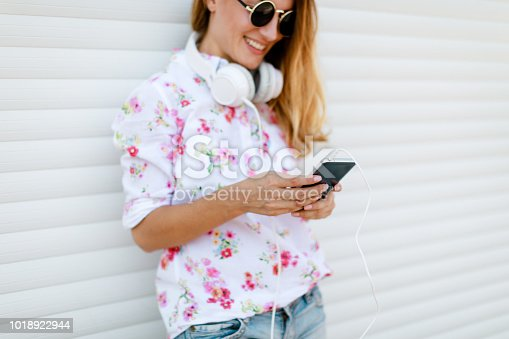 istock Beautiful young woman using mobile in the street 1018922944