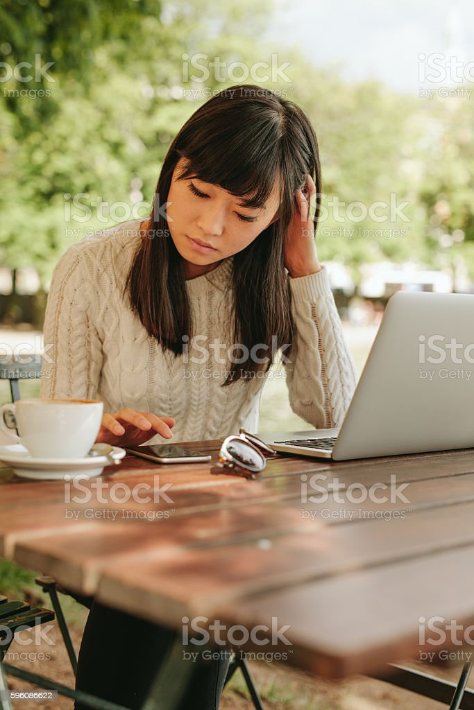 Beautiful young woman using mobile phone at cafe royalty-free stock photo