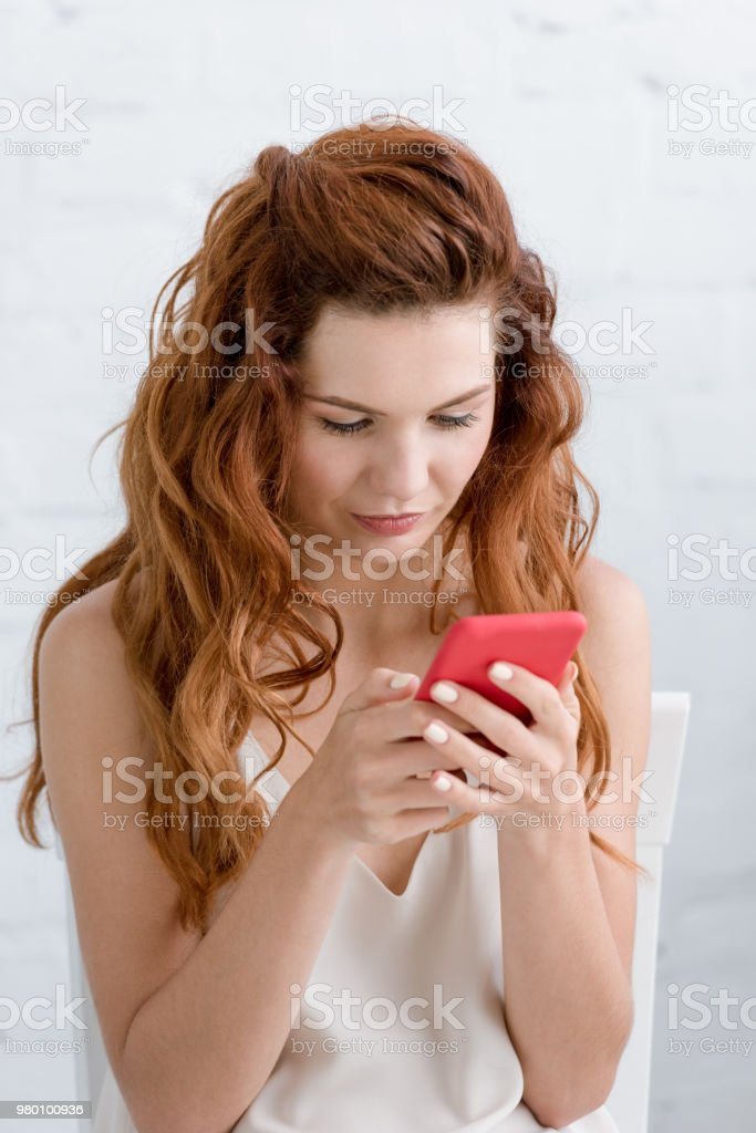 beautiful young woman using smartphone at home stock photo