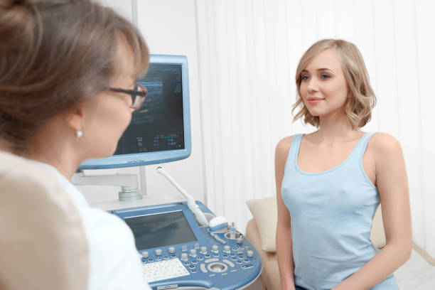Beautiful young woman visiting doctor stock photo