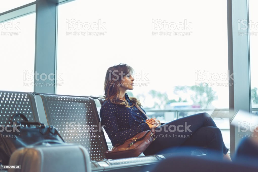 Beautiful young woman waiting her flight at airport stock photo