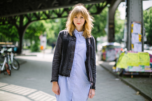 Portrait of beautiful young woman walking on the city street. Attractive female wearing a jacket looking at camera and smiling.