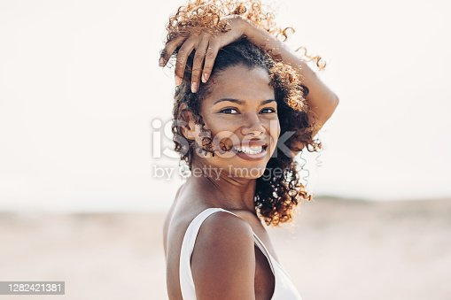 Beautiful young black woman walking on the beach