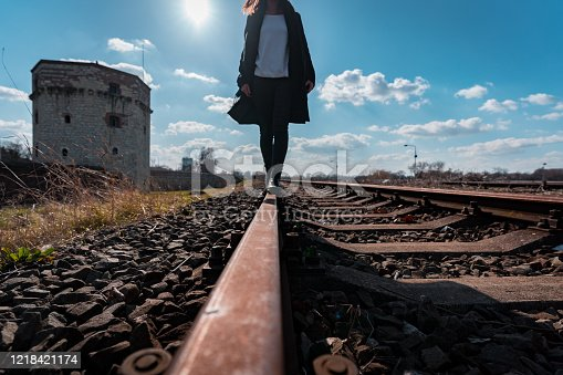 Young woman walking on the railroad tracks with Kula Nebojsa tower in the background in Belgrade
