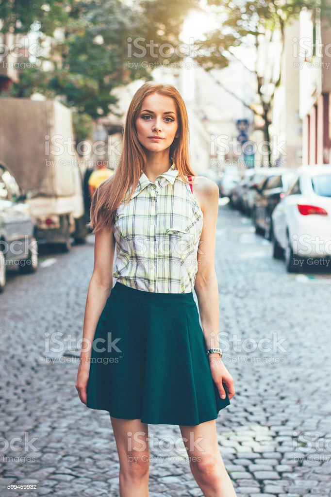 Beautiful young woman walking on the street stock photo